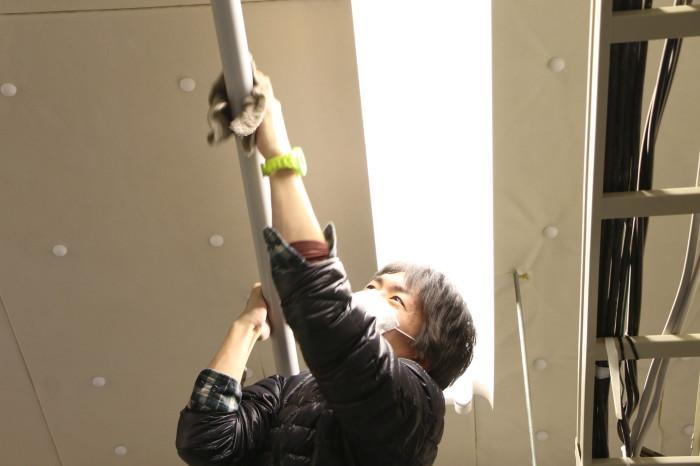 教室にある照明機材を吊れるバーの上を拭いています。